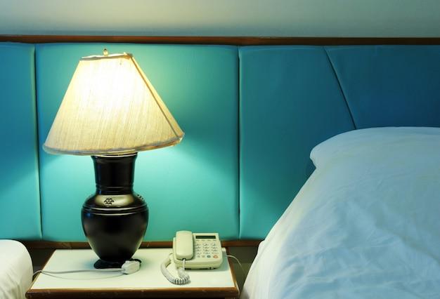 Lámpara de mesa y teléfono en el dormitorio