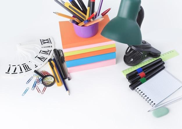 Lámpara de mesa y útiles escolares de colores sobre fondo blanco .foto con espacio de copia.