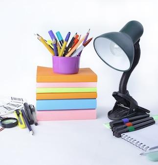 Lámpara de mesa y útiles escolares sobre fondo blanco.