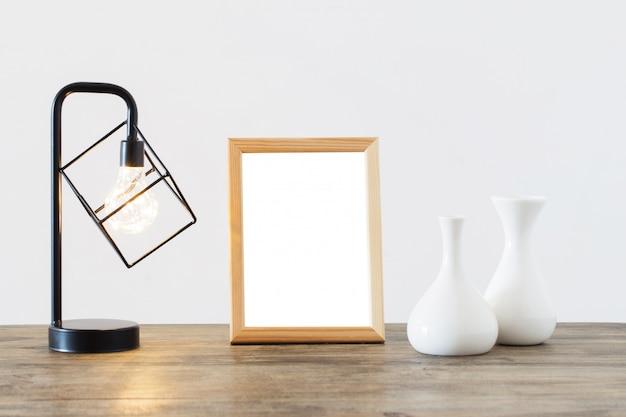 Lámpara de metal negro, jarrones y marco de madera en interior blanco.