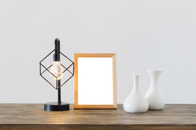Lámpara de metal negro y marco de madera en interior blanco.