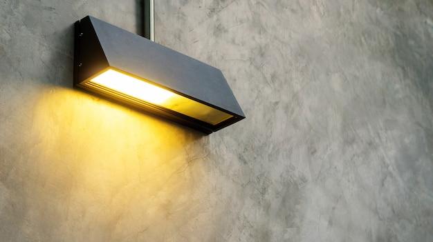 Lámpara negra brilla en una pared gris.