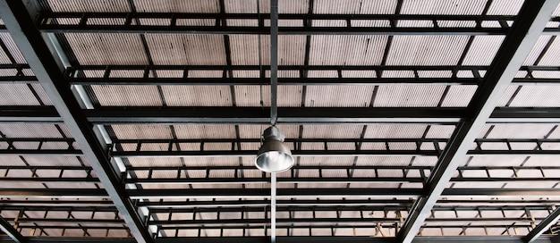 Lámpara de red de metal colgando bajo techo de zinc