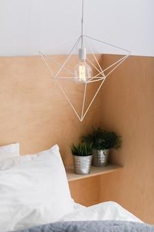 Lámpara de techo blanca geométrica de estilo loft con fondo de madera claro y una bombilla de edison.