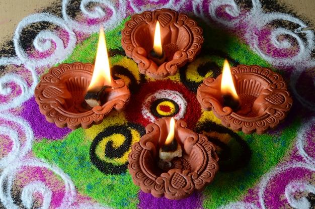 Lámparas de arcilla diya encendidas durante la celebración de diwali, rangoli en segundo plano.