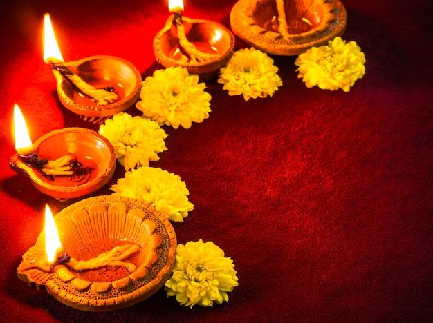 Lámparas diya de arcilla tradicionales encendidas con flores para la celebración del festival diwali
