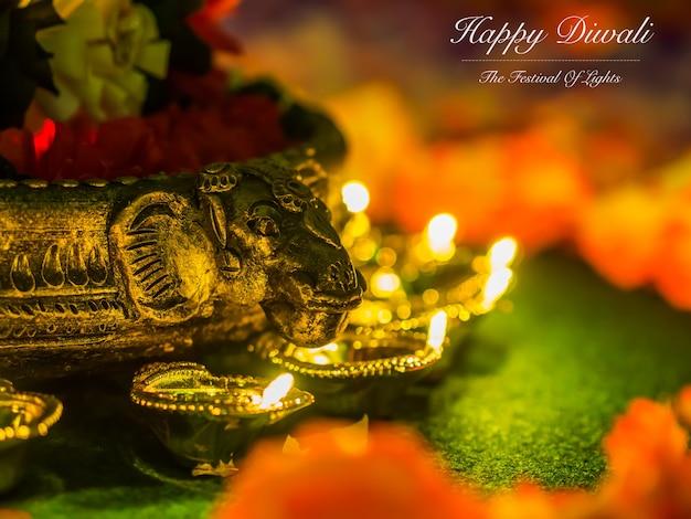Lámparas diya de arcilla tradicionales iluminadas con flores para la celebración del festival diwali.