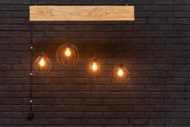 Lámparas retro naranjas colgando de una tabla de madera sobre un fondo de pared de ladrillo negro oscuro. plantilla moderna con lugar para publicidad o texto. diseño de interiores colgantes de luz