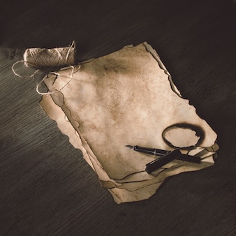 Lana de hilo y bolígrafo de tinta cerca del papel quemado