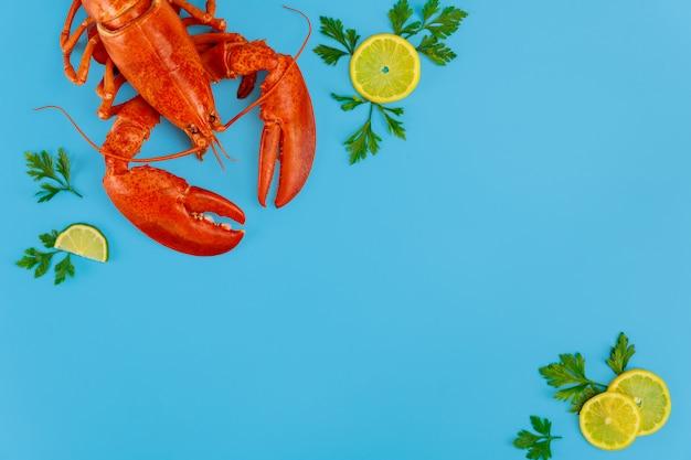 Langosta de cangrejo preparada con cítricos y perejil sobre superficie azul.