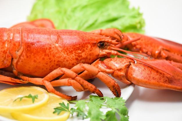 Langosta de marisco deliciosa en un plato blanco con limón cilantro y ensalada de lechuga / primer plano de la comida de langosta al vapor