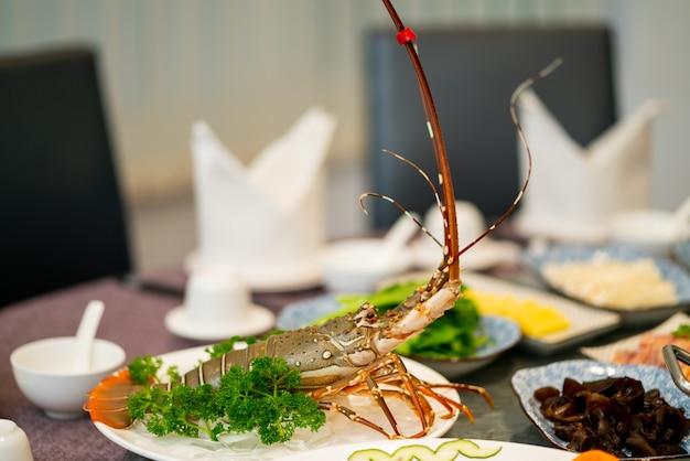 Langosta con perejil en un plato blanco redondo cerca de otros platos