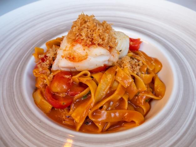 Langosta a la plancha con pasta en el plato, cocina mediterránea.