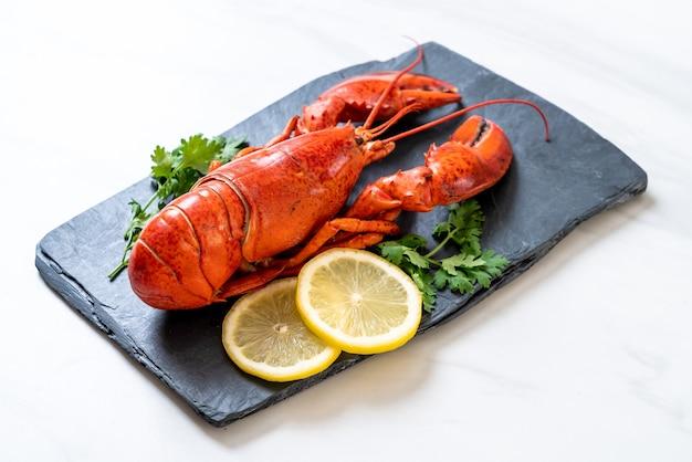 Langosta roja con verduras y limón sobre placa de pizarra negra