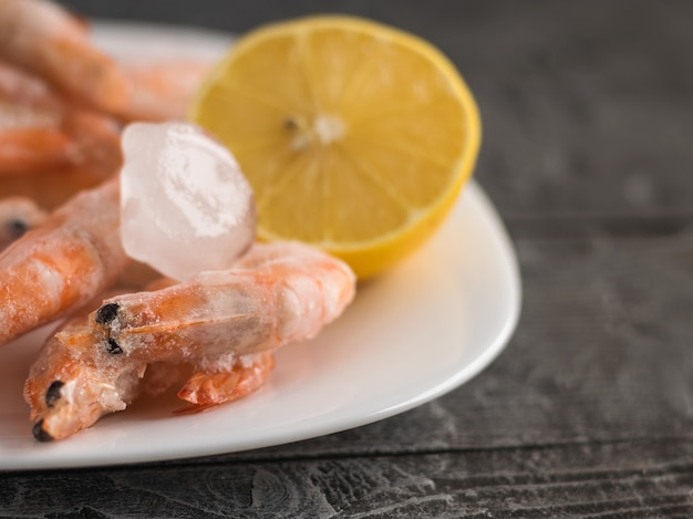 Langostinos congelados en un cuenco de barro blanco con limón sobre una mesa de madera oscura.