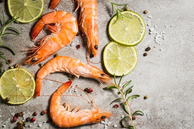 Langostinos con especias de lima, limón, romero y pimienta negra sobre piedra. gambas frescas sabrosas listas para ser cocinadas.