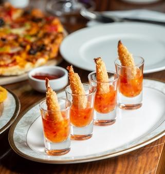 Langostinos fritos crujientes servidos en vasos de chupito con salsa de chile dulce
