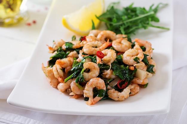 Langostinos fritos o gambas con espinacas, chile y ajo en plato blanco.