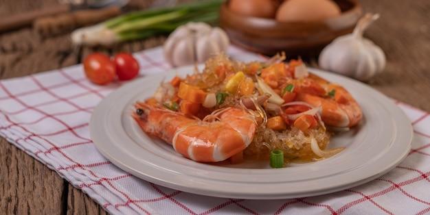 Langostinos salteados con fideos de vidrio en un plato blanco colocado sobre un paño con huevos y ajo.