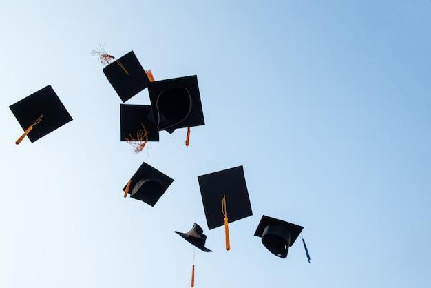 Lanza un sombrero negro de graduados en el cielo.