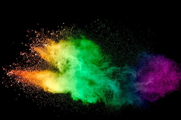 Lanzamiento de polvo multicolor sobre superficie negra.