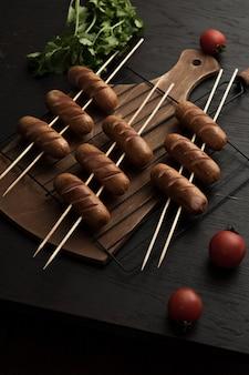 Lanzamiento vertical de alto ángulo de salchichas a la parrilla y tomates cherry sobre una superficie de madera