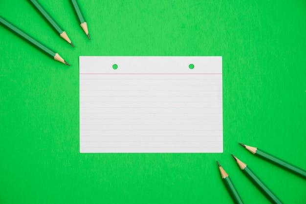Lápices afilados y papel de línea con textura sobre fondo verde brillante