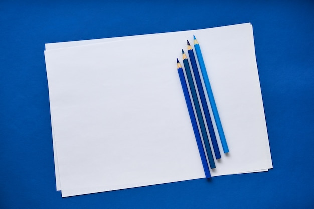 Lápices azules y una hoja de papel blanco sobre un fondo coloreado