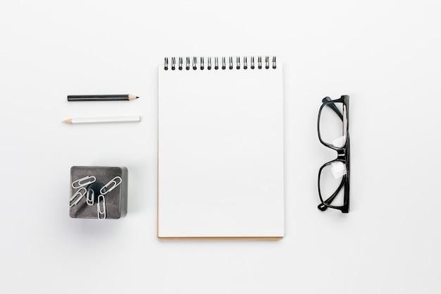 Lápices en blanco y negro con bloc de notas en espiral, clips en imán con lentes en el escritorio de oficina