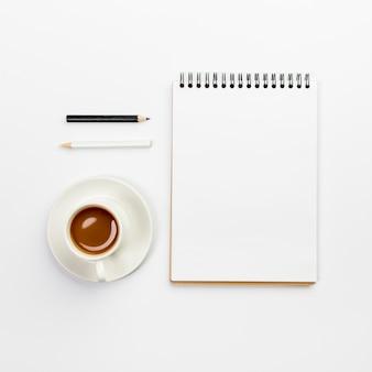 Lápices blancos y negros con la taza de café y la libreta espiral en blanco en el escritorio de oficina