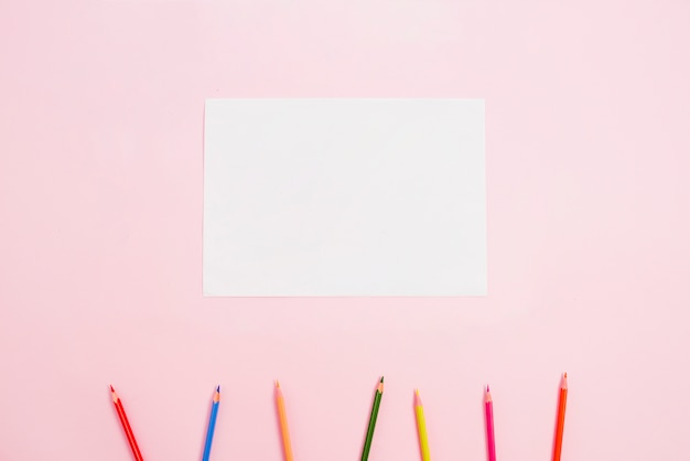 Lápices brillantes con papel en blanco en la mesa