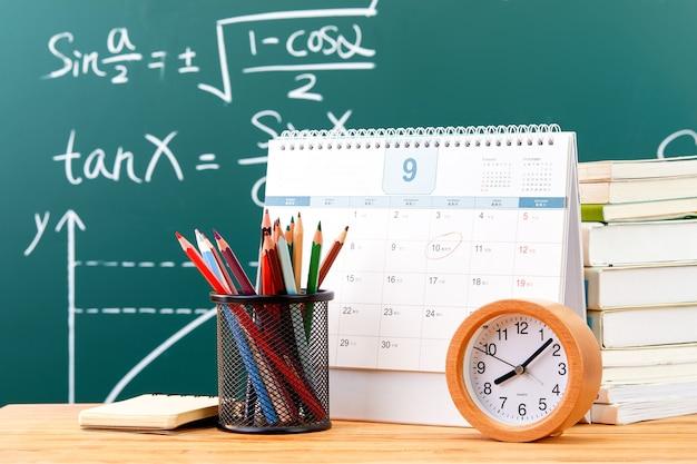 Lápices, un calendario, un reloj y algunos libros junto a la pizarra.