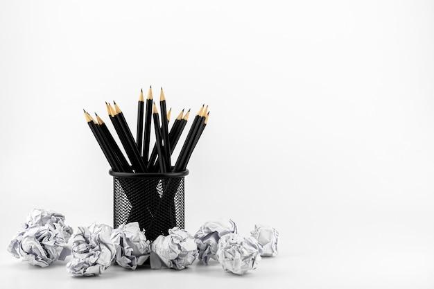Lápices en la cesta y bola de papel arrugado sobre una mesa blanca. - concepto de ideas de trabajo y negocios.