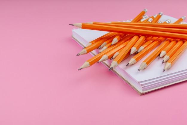 Lápices de color naranja en el cuaderno. concepto de arte
