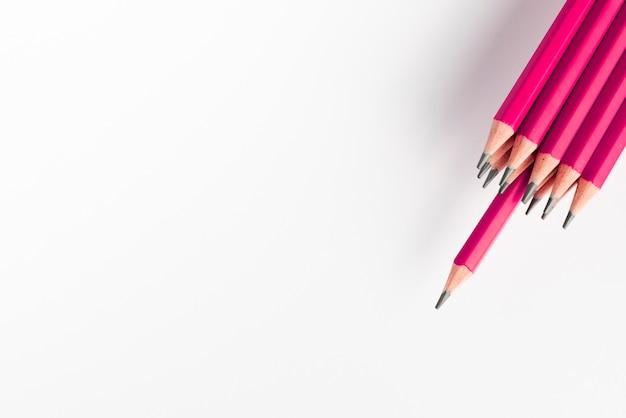 Lápices de color rosa afilado montón contra el fondo blanco.