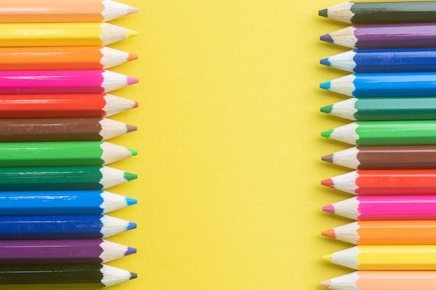 Lápices de color sobre fondo de papel amarillo.