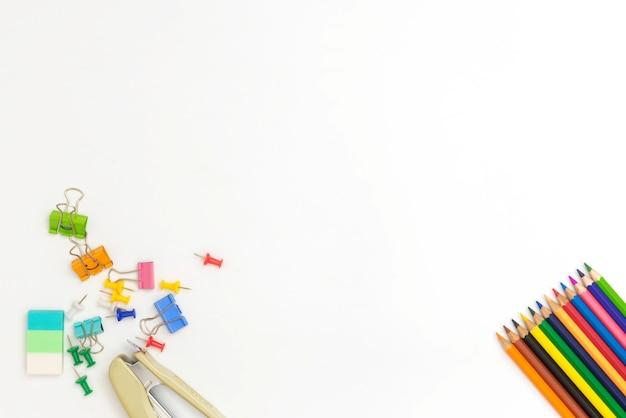 Lápices de colores y accesorios sobre fondo blanco con copyspace