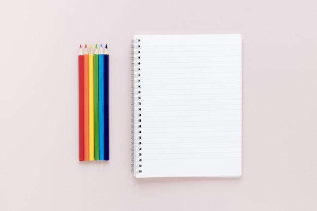 Lápices de colores al lado del cuaderno