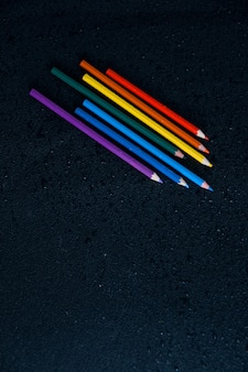 Lápices de colores del arco iris en un backgruond negro húmedo símbolo lgbt copia espacio gotas de agua