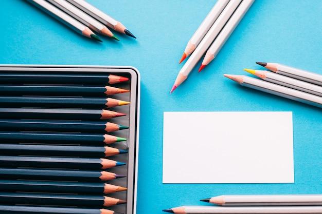 Lápices de colores en caja con tarjeta de papel en blanco sobre escritorio azul.