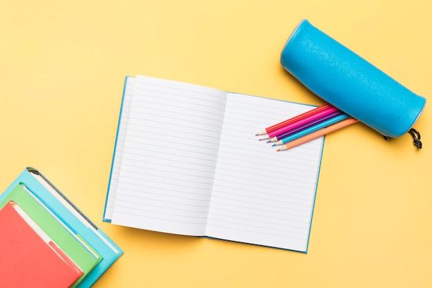 Lápices de colores compuestos en cuaderno abierto con páginas vacías