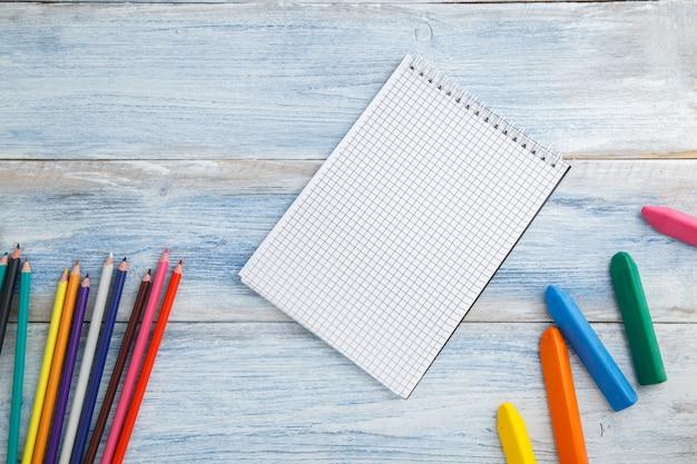 Lápices de colores, crayones y bloc de notas en madera vintage desgastada azul y blanca, vista superior