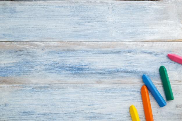 Lápices de colores y crayones sobre una madera vintage desgastada azul y blanca, vista superior