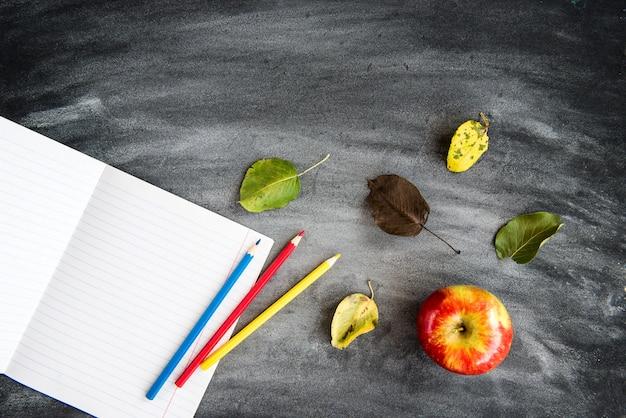 Lápices de colores, cuaderno sobre fondo de tablero negro. volver al concepto de escuela.