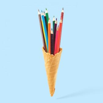 Lápices de colores en un cuerno de galleta. concepto creativo