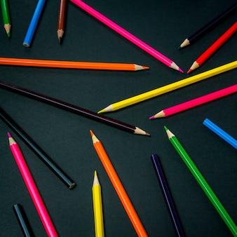 Lápices de colores esparcidos por todo el marco sobre un fondo negro. vista plana, vista superior