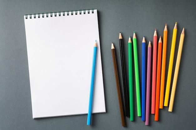 Lápices de colores en fila aislados en la vista superior de la pared gris. cuaderno de espiral con lápiz de color sobre la mesa vacía. concepto de endecha plana