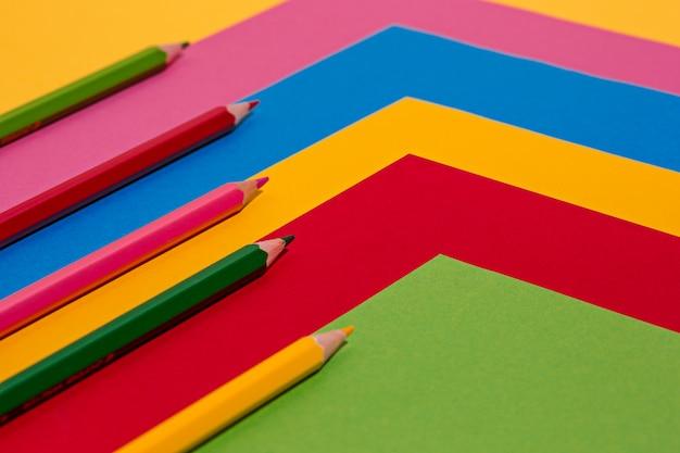 Lápices de colores y hojas de papel de colores.