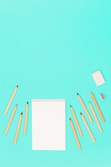 Lápices de colores de madera y bloc de dibujo abierto para dibujar.