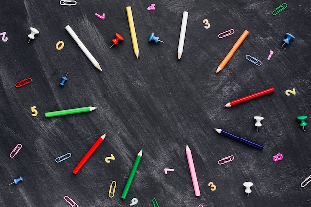 Lápices de colores y marcadores con clips de papel esparcidos en la pizarra